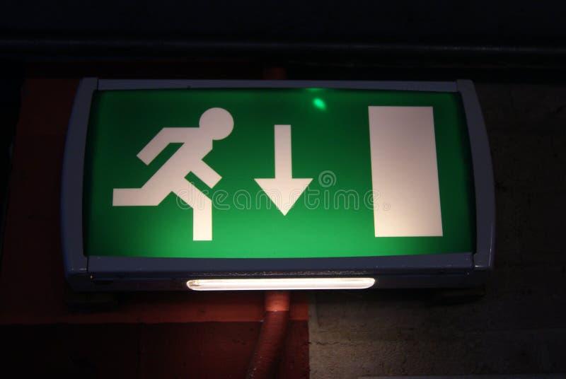 Wyjście ewakuacyjne backlit zieleń znak fotografia stock