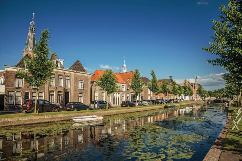 Wykładający kanał z łodzią, kościelny dzwonkowy wierza i cegła domami przy bankiem na zmierzchu w Weesp, zdjęcia royalty free