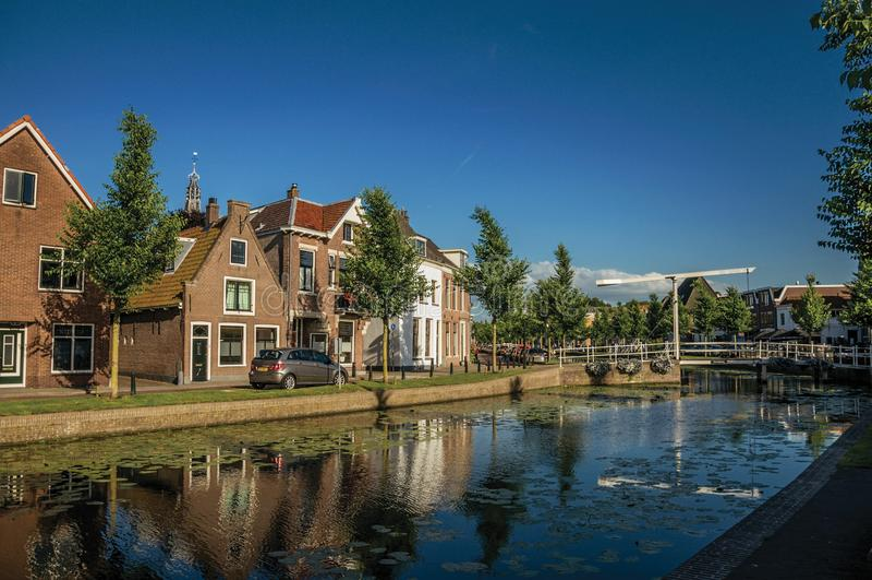 Wykładający kanał z nadwodnymi roślinami, bascule mostem i cegła domami przy bankiem na zmierzchu w Weesp, zdjęcie royalty free