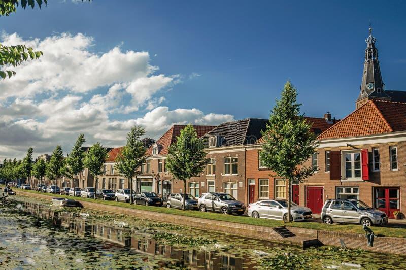 Wykładający kanał z nadwodnymi roślinami, bascule mostem i cegła domami przy bankiem na zmierzchu w Weesp, obraz royalty free