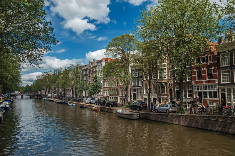 Wykładający kanał z starymi ceglanymi domami, łodziami i pogodnym niebieskim niebem w Amsterdam, fotografia stock