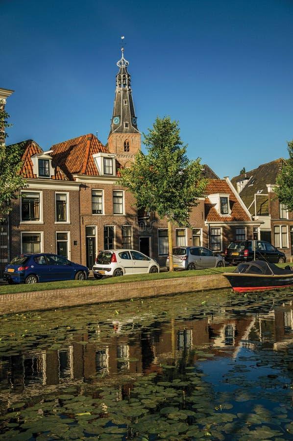 Wykładający kanał z steeple, cegła domami i cumującą łodzią na zmierzchu w Weesp, obrazy royalty free