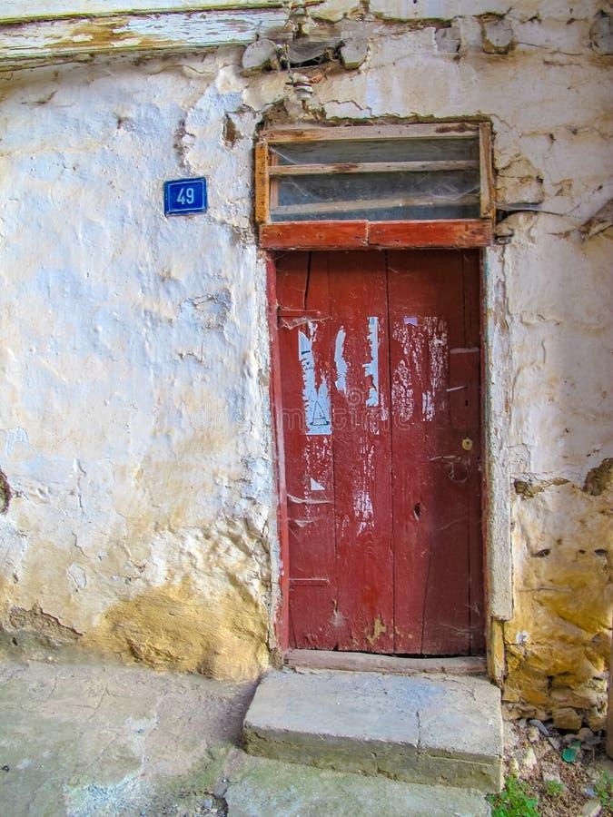 Wykolejena dom z nieociosanym starym drzwi zdjęcia stock