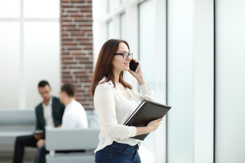 Wykonawcza biznesowa kobieta opowiada na telefonie komórkowym z schowkiem zdjęcia stock
