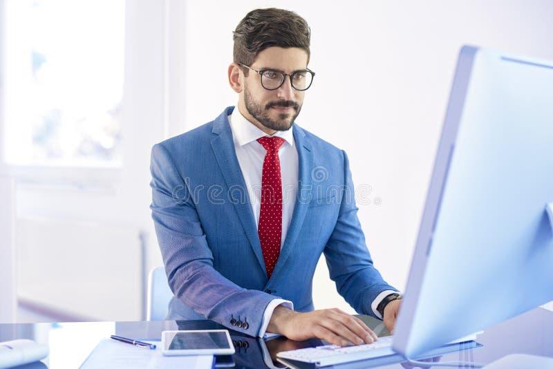 Wykonawczy biznesmen używa komputer w biurze obraz stock