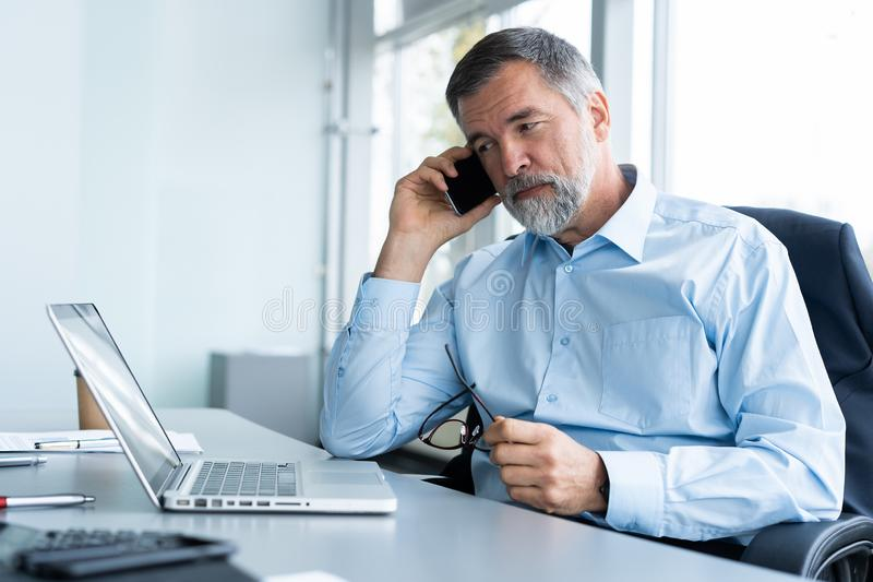 Wykonawczy starszy biznesmen używa jego telefon komórkowego i opowiadający z somebody w biurze podczas gdy pracujący laptop obrazy stock