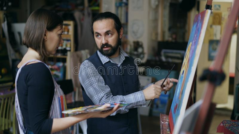 Wykwalifikowana artysty mężczyzna nauczania młoda dziewczyna rysować obrazy i wyjaśniać podstawy światło w sztuki studiu obrazy royalty free