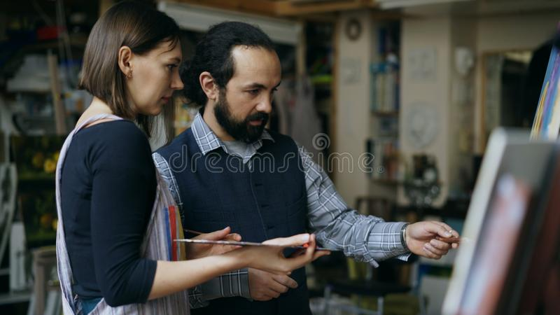 Wykwalifikowana artysty mężczyzna nauczania młoda dziewczyna rysować obrazy i wyjaśniać podstawy światło w sztuki studiu zdjęcia stock