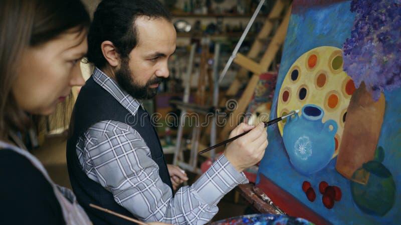 Wykwalifikowana artysty mężczyzna nauczania młoda dziewczyna rysować obrazy i wyjaśniać podstawy w sztuki studiu fotografia royalty free