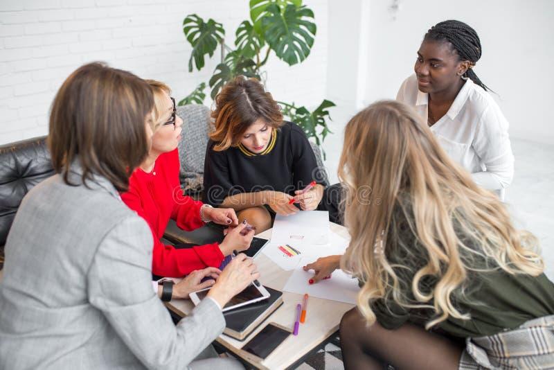 Wykwalifikowani wielokulturowi żeńscy bloggers dyskutuje nowych tematy dla medialnej strony internetowej zdjęcie stock