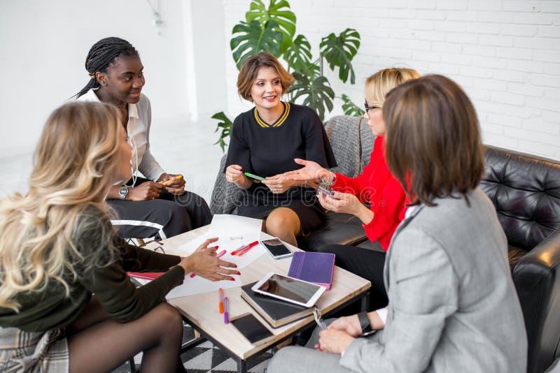 Wykwalifikowani wielokulturowi żeńscy bloggers dyskutuje nowych tematy dla medialnej strony internetowej fotografia royalty free
