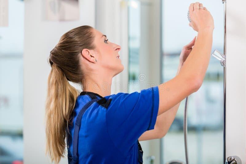 Wykwalifikowany żeński pracownik sprawdza showerhead w nowożytnym sanitarnym artykuły sklepie obraz stock