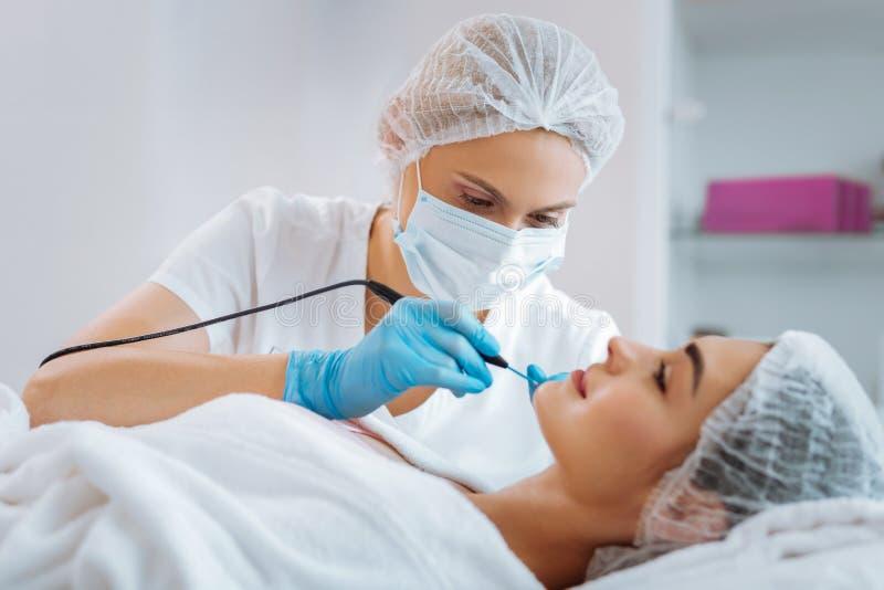 Wykwalifikowany fachowy żeński dermatolog usuwa gramocząsteczki fotografia stock