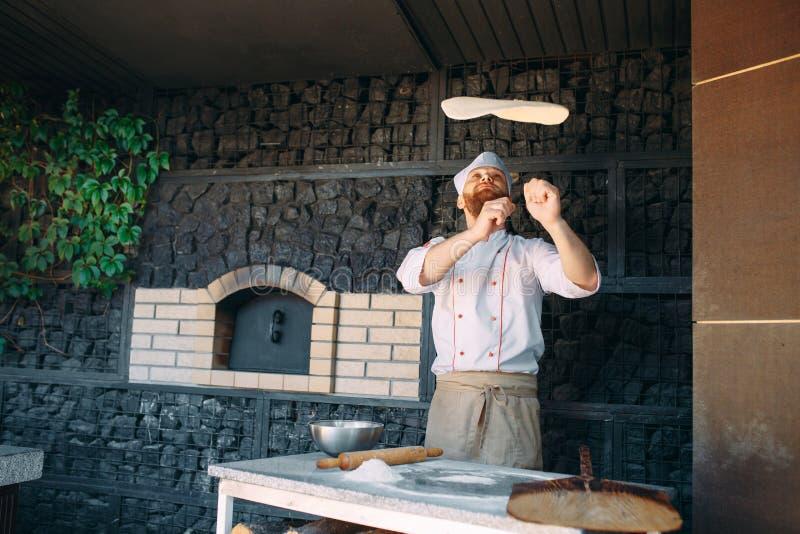Wykwalifikowany szefa kuchni narządzania ciasto dla pizzy kołysania się z rękami i rzucać w górę zdjęcia royalty free