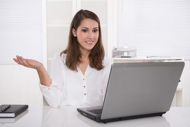 Wymarzona praca: pomyślny bizneswomanu obsiadanie przy biurkiem z laptopem zdjęcia royalty free