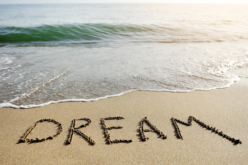 Wymarzony słowo pisać na plażowym piasku - pozytywny myślący pojęcie obrazy royalty free
