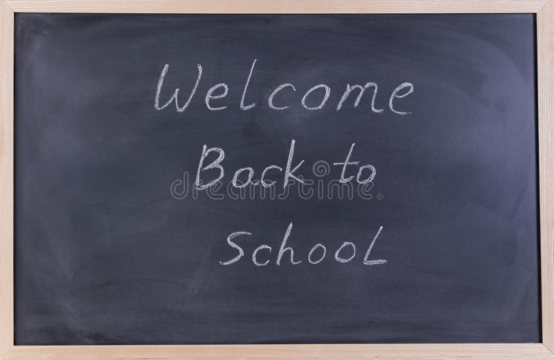 Wymazujący czarny chalkboard z powitaniem szkoły wiadomość dla z powrotem obraz stock