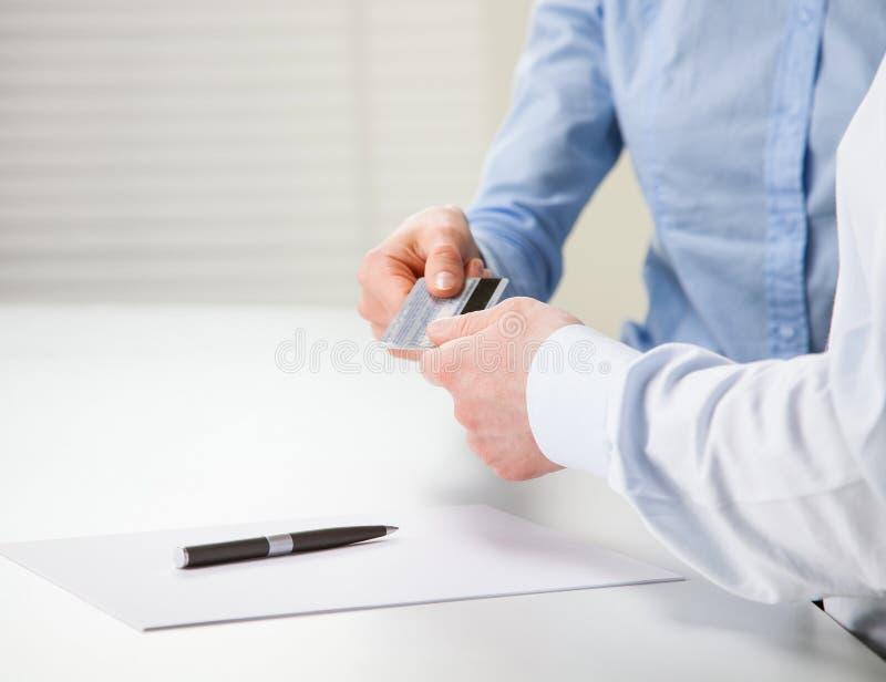 Wymieniać kredytową kartę nad stołem obraz stock