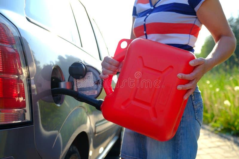 Wymuszona przerwa Wyczerpywał gaz w zbiorniku samochód Kobieta wypełnia samochód z benzyną od dodatkowego zbiornika Kanister 10 l zdjęcia royalty free