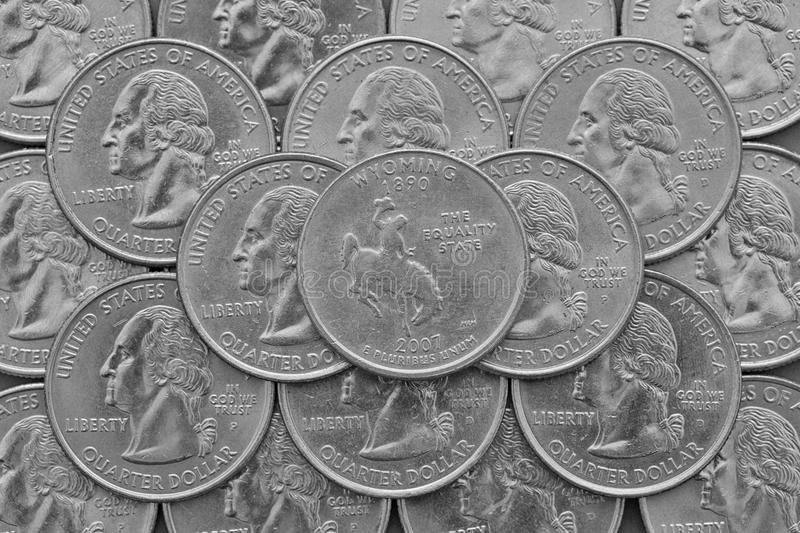 Wyoming State and coins of USA. Pile of the US quarter coins with George Washington and on the top a quarter of Wyoming State stock photography