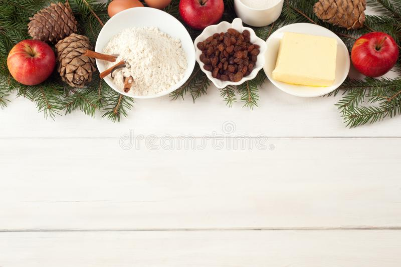 Wypiekowi składniki na bielu stole jajka, masło, pikantność, jabłka, rodzynki, wanilia, cynamonowi kije, biała mąka i xmas drzewo fotografia royalty free