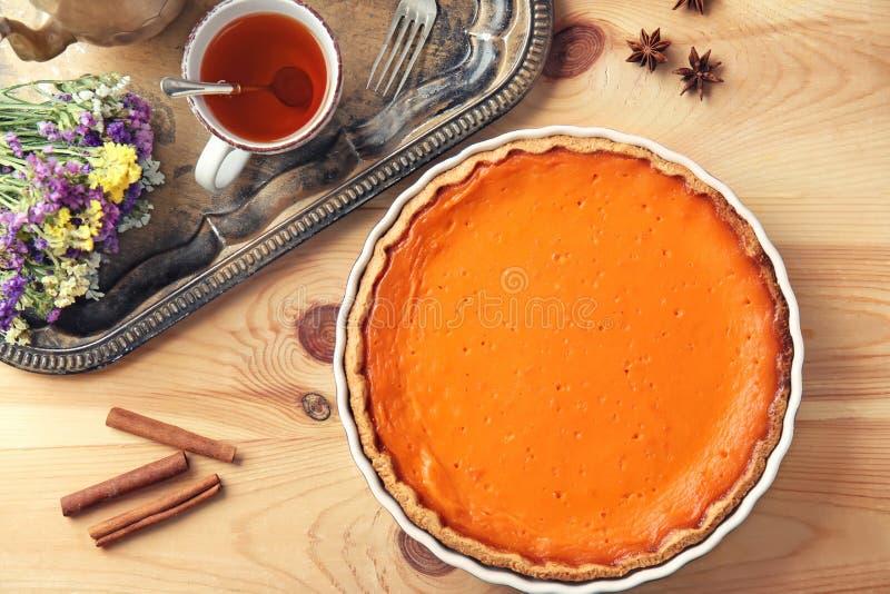 Wypiekowy naczynie z smakowitym dyniowym kulebiakiem i filiżanką herbata na drewnianym stole fotografia stock