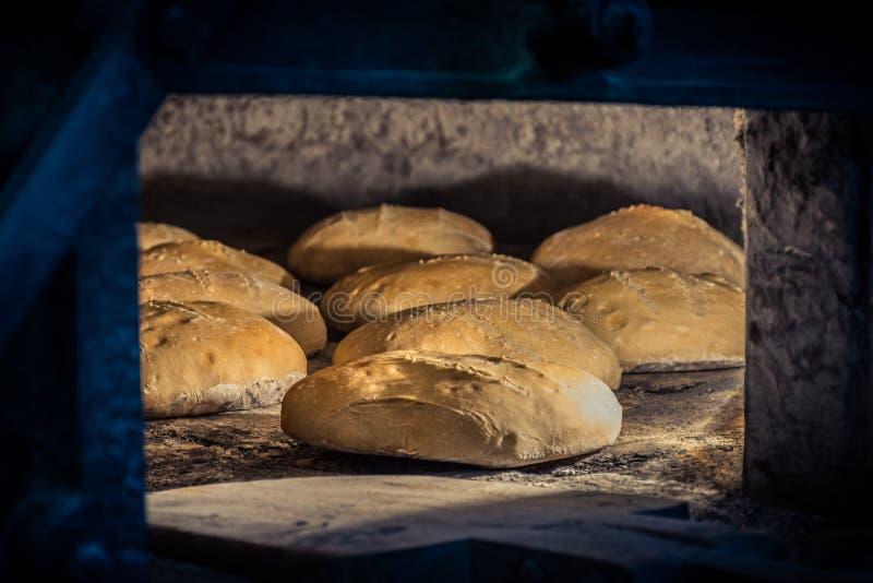 Wypracowanie chleb w tradycyjnym drewnianym piekarniku obrazy stock