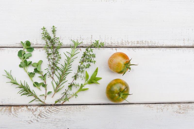 Wyprodukowany lokalnie ziele i pomidory na nieociosanym drewnie wsiadają zdjęcia stock