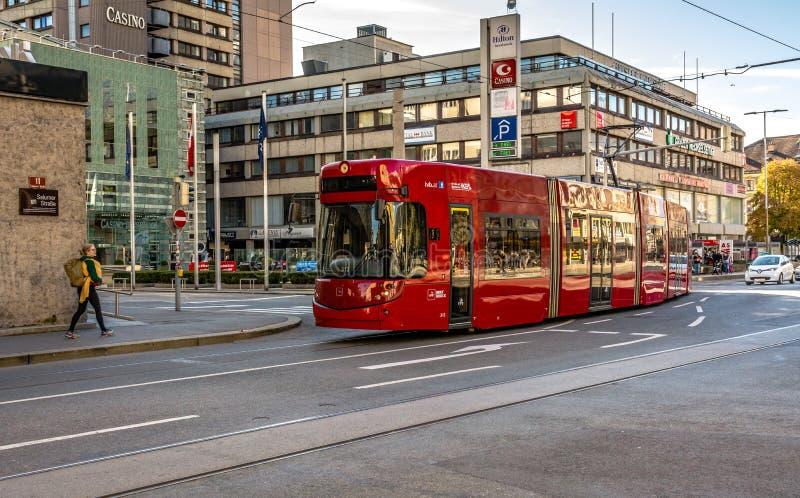 Wyróżniający czerwony tramwaj który biega przez miasta Innsbruck, Austria, Europa zdjęcia royalty free