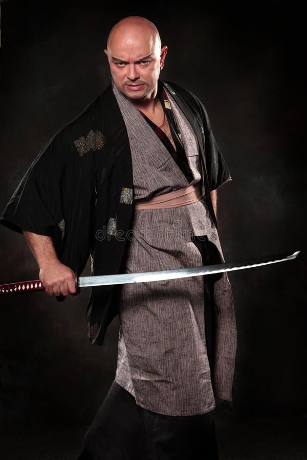 Wyrażeniowy mężczyzna w wizerunku samuraj z kordzikiem w ręce zdjęcia stock