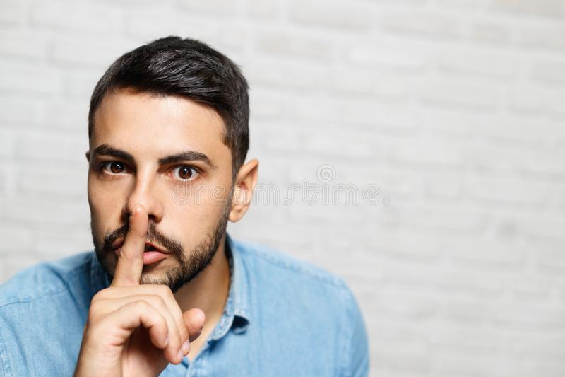 Wyrazy Twarzy Młody broda mężczyzna Na ściana z cegieł zdjęcie stock