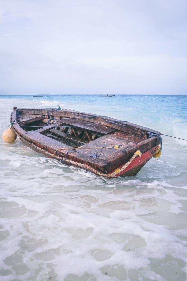 Wyrzucać na brzeg łódź w Zanzibar w piankowych falach obrazy royalty free