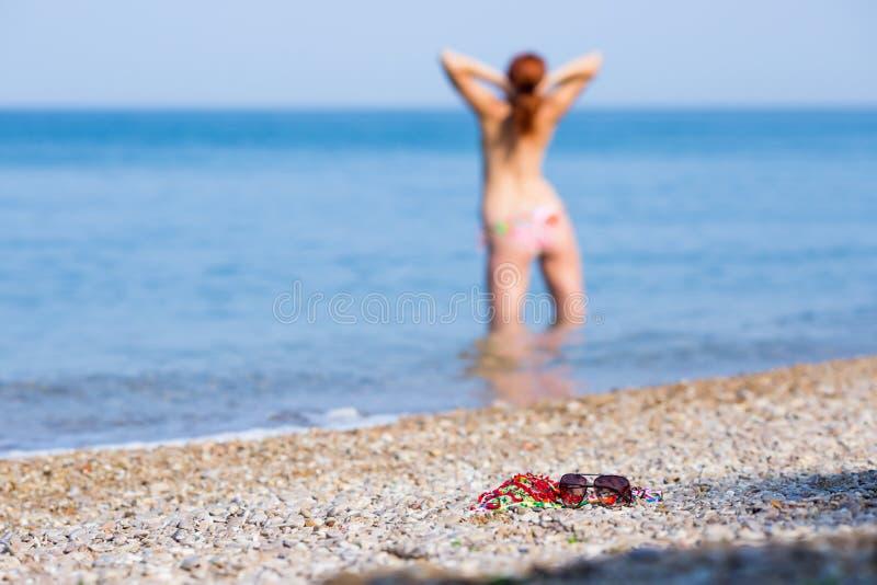 Wyrzucać na brzeg spokojnego życie od zabarwiającego bikini wierzchołka i okularów przeciwsłonecznych obrazy royalty free