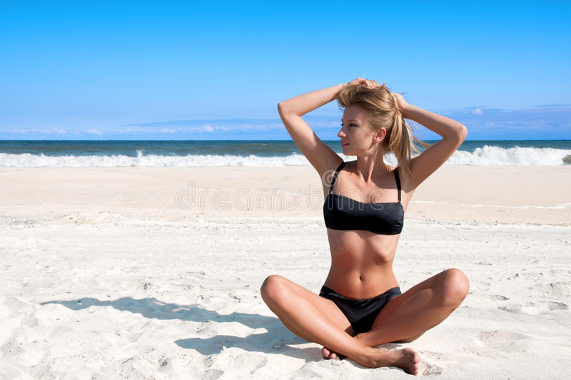 Wyrzucać na brzeg wakacje Piękna garbnikująca kobieta relaksuje na tropikalnej plaży w bikini zdjęcie royalty free