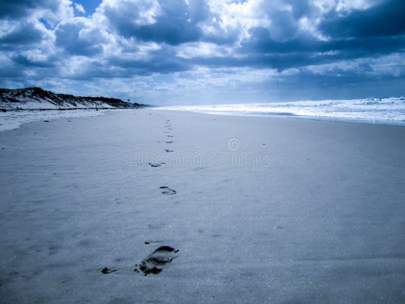 Wyrzucać na brzeg z odciskami stopy prowadzi w nieskończonego fotografia stock