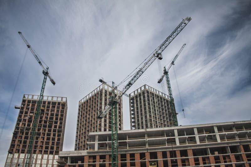 Wysocy kondygnacja budynki w budowie Basztowi żurawie zbliżają budynek Aktywność, architektura zdjęcie stock