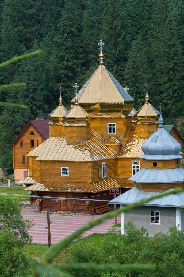 Wysocy spiers nad złotymi dachami kościół przeciw tłu zieleni świerkowi drzewa zdjęcie royalty free