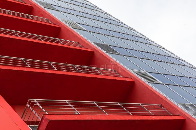 Wysoka elewacja budynku nowoczesnego z terakotą, jasnopomarańczową ścianą parkietową, oknami balkonowymi i szklanymi, widokiem di zdjęcia royalty free