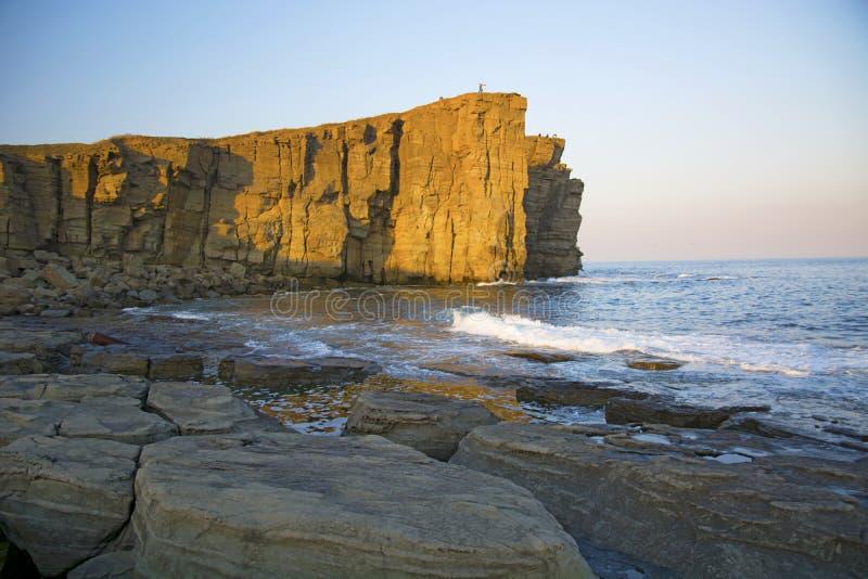 Wysoka faleza nad morze faleza pochodzi w morze, dużo chełbotanie machają i kamienie obrazy royalty free