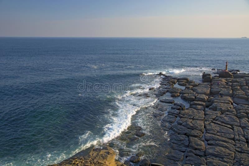 Wysoka faleza nad morze faleza pochodzi w morze, dużo chełbotanie machają i kamienie fotografia stock