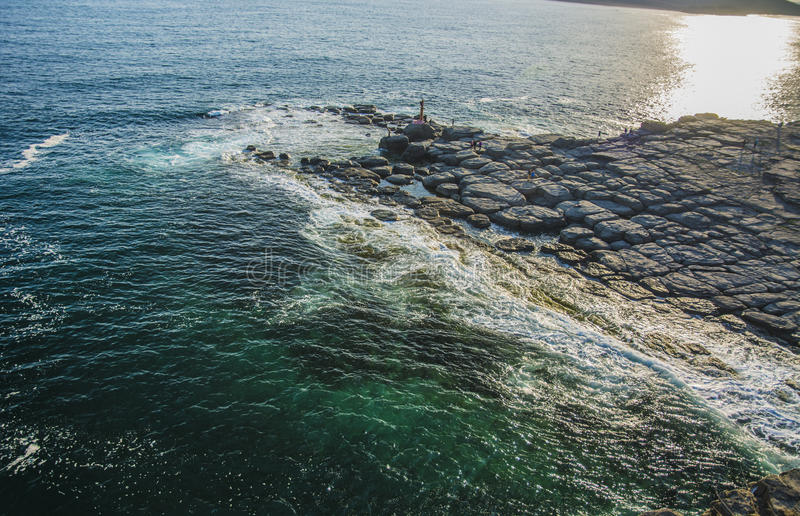 Wysoka faleza nad morze faleza pochodzi w morze, dużo chełbotanie machają i kamienie obrazy stock