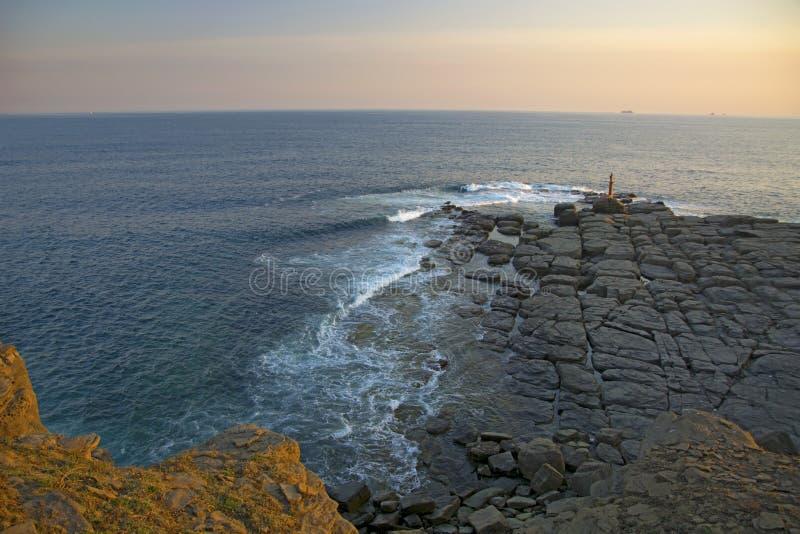 Wysoka faleza nad morze faleza pochodzi w morze, dużo chełbotanie machają i kamienie obraz stock