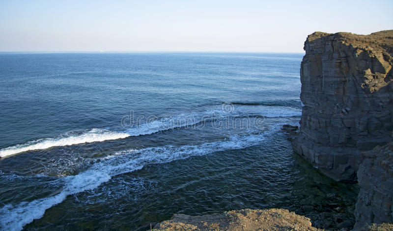 Wysoka faleza nad morze faleza pochodzi w morze, dużo chełbotanie machają i kamienie zdjęcie royalty free