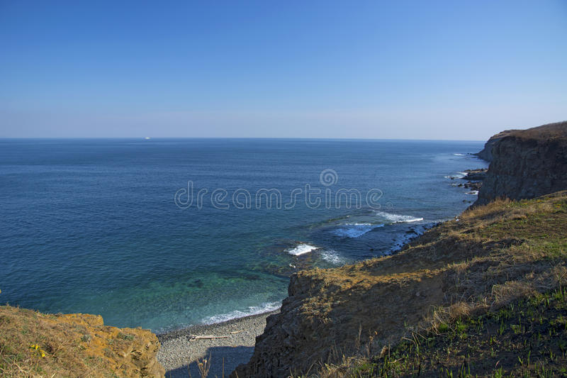 Wysoka faleza nad morze faleza pochodzi w morze, dużo chełbotanie machają i kamienie zdjęcia stock