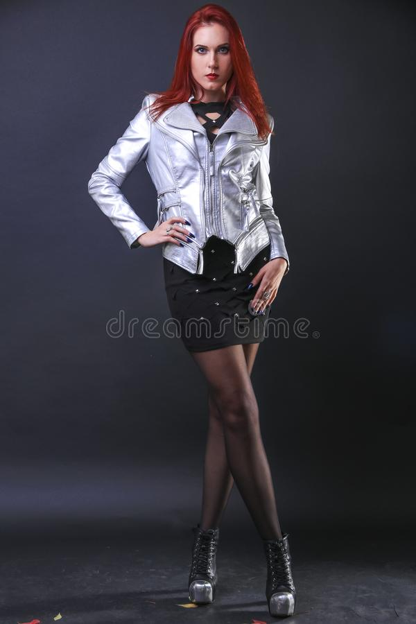 Wysoka wspaniała czerwieni głowy dziewczyna pozuje w srebnej motocykl kurtce w studiu obraz stock