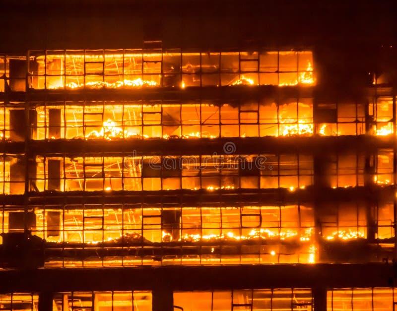Wysoki budynek na pożarniczych, dużych ogieniach burnning/ obrazy stock
