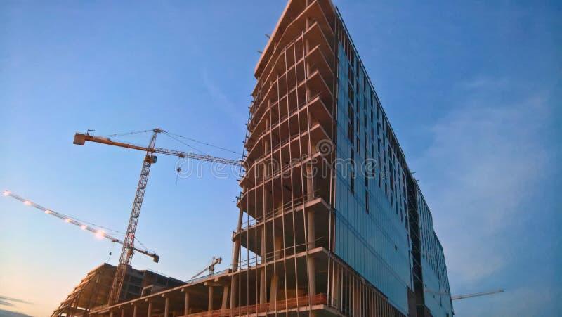 Wysoki budynek w budowie z basztowymi żurawiami w wieczór obraz stock