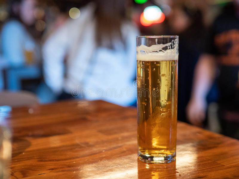 Wysoki chuderlawy szkło złoty lager piwa obsiadanie na baru kontuaru ludziach w tle zdjęcia royalty free