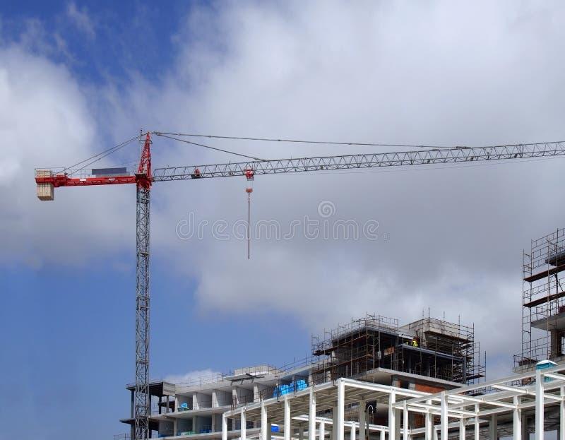 Wysoki czerwony żuraw na wielkiej budowie z metal strukturą rusztuje niebieskie niebo i chmury zdjęcie royalty free