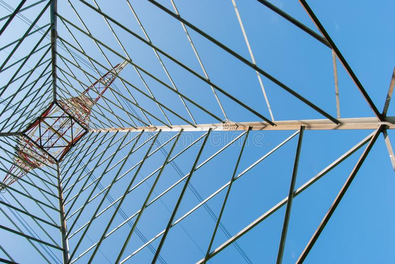 Wysoki elektryczny pilon i niebieskie niebo widzieć spod spodu zdjęcie stock